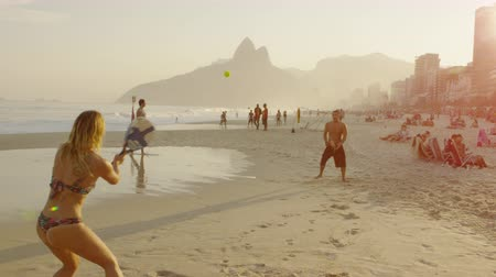 brasileiro : Reverse angle slow motion, dolly out footage of a girl playing tennis on Ipanema beach with a guy, who stumbles out of frame to hit the ball Vídeos