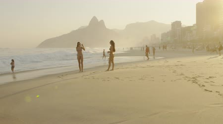 Рио : Slow motion, tracking shot of two young women in bikinis on Ipanema beach against the background of Dois Irmos and the cityscape at dusk