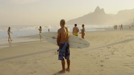 Рио : Slow motion tracking shot of a man holding a short surfboard watching the waves. Men and women stand nearby. Filmed in Rio de Janeiro, Brazil.