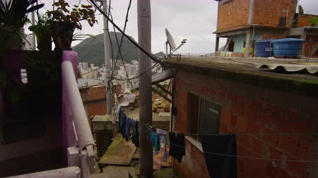 indigence : Slow motion dolly shot of men and women in a favela in Rio de Janeiro, Brazil. A man is seen looking up, holding a long stick and poking something. Stock Footage