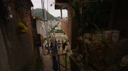 Рио : Slow motion dolly shot - turning a corner and going downstairs in a favela in Rio de Janeiro, Brazil taken with a high speed camera. Стоковые видеозаписи