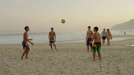 juventude : Slow motion pan of boys standing in a circle and kicking a football to each other. Filmed at Ipanema beach, Rio de Janeiro, Brazil.