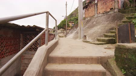 juventude : Tracking shot on a concrete path in a brazilian favela. A young boy and a man holding a kite can be seen