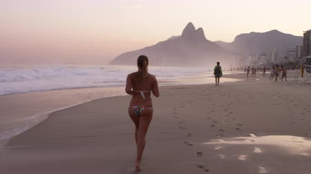 Рио : Tracking shot of a woman jogging down Ipanema beach at dusk. She passes others enjoying the beach, and ocean waves crash next to her. Filmed in Rio de Janeiro, Brazil.