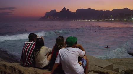 сумерки : Pan of people sitting on rocks and watching the waves roll in at sunset. People are swimming and surfing and the lights of Rio, Brazil are shining in the background.
