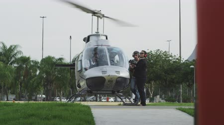 heliport : Slow motion footage of a helicopter sitting at the Lagoa heliport in Rio de Janeiro, Brazil. The pilot sits at the controls while a man prepares to board and a woman instructs him.