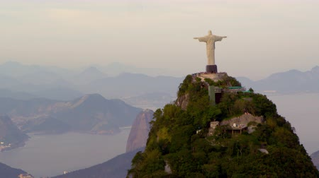 Рио : Aerial tracking footage of the Christ Redentor statue that stands on Corcovado mountain, overlooking Rio de Janeiro, Brazil, Guanabara Bay, and the mountains surrounding them . Tourists are crowded at the overlook points near the statue.