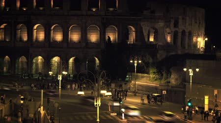 arch of constantine : Footage of a busy intersection near the Colosseum. The Forum is illuminated for the night.