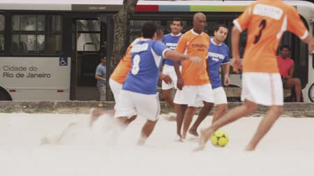 Рио : Slow motion shot of men playing soccer game at Tavares Bastos Favela in Rio de Janeiro, Brazil. The camera pans left to right as it follows the soccer teams movements. Стоковые видеозаписи