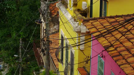 mozog e fel : Tilting shot of a middle class neighborhood and a favela in Rio de Janeiro, Brazil. The camera moves from the bottom, where the middle class neighborhood is seen. As it moves up, the favela near this neighborhood can be seen.