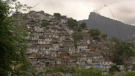 indigence : Blurred static shot of shanties at the base of Corcovado Mountain in Rio de Janeiro, Brazil. The shot was taken during the day. The statue of Christ the Redeemer can be seen at the top of the mountain.