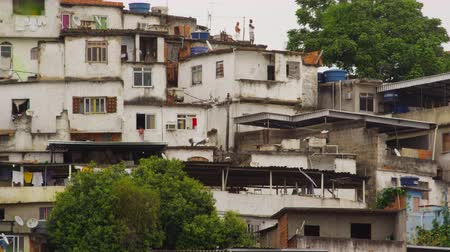 indigence : Static shot of a part of a favela in Rio de Janeiro, Brazil. Some peoples can be seen on top of some of the roofs of the dirty buildings.