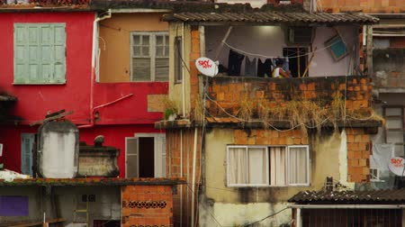 Рио : Slow motion shot of a woman hanging up her laundry on the balcony of her home. Takes place in a favela of Rio de Janeiro, Brazil