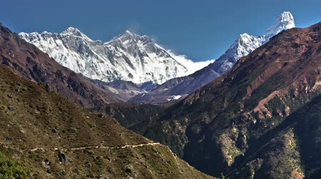 nuptse : Time-lapse of Everest Base camp trekkers walking along the Khumjung mountainside trail in the Sagarmath National Park in Nepal.  Mount Everest,Nangkar,Tengboche,Pokaide,and Ama Dablam are in the background Stock Footage