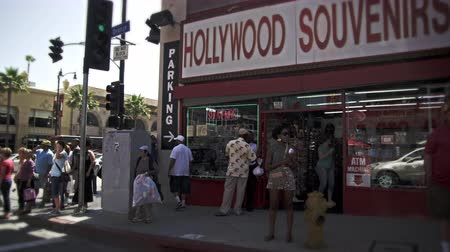 áru : Slow motion dolly shot of Hollywood Blvd. in California. The Hollywood Souvenirs shop is seen in the shot along with some people on the street. This was taken in June 2012