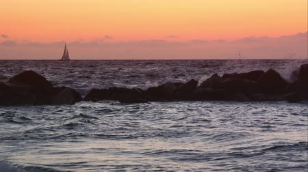 sunset sea : Slow motion view of sailboat on the horizon at sunset.