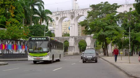 Рио : Cars traveling under an aqueduct in Rio de Janeiro, Brazil. Slow motion of a busy street. Стоковые видеозаписи