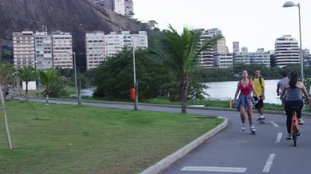 Рио : Slow motion, tracking shot of a couple rollerblading and skateboarding going past a people on bicycles with skyscrapers and buildings in the distance, traveling down a lakeside street in Rio de Janeiro, Brazil. Стоковые видеозаписи