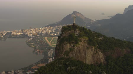 латинский : Helicopter footage of Christ the Redeemer Statue and Lagoa. The buildings of Rio de Janeiro and the mountains rocky face are displayed in the video, also. Стоковые видеозаписи