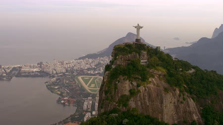 definição : Lagoa, Cristo Redentor, Rio de Janeiro, and the Atlantic - aerial footage. The steep face of the mountain that the Cristo statue resides upon highly defined as are the colors of the region.