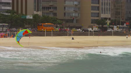 otobüs : Panning shot of parasailing surfer coming into the shore. The sail is green, blue and red. waves are white and tide is high. Beach is sandy. Buildings are visible in the background. An orange bus is parked along the street along with other plain looking b Stok Video