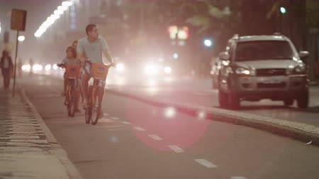 Рио : Shot of biking lane with bikers and runners. The lane is separated by a median. On the other side of the median is where the traffic is. Traffic is busy. Vehicles are passing and driving with their lights on. Vehicles lights cause lens flare. Filmed at ni