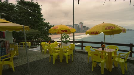 обедающий : Slow motion dolly shot of outdoor cafe in Copacabana, Rio de Janeiro, Brazil. The name Praia Skol 360 is seen on the yellow umbrellas that cover the yellow tables and chairs.