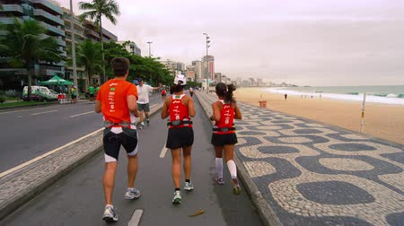 Рио : Slow tracking shot of three runners running along the street near Ipanema beach in Rio de Janeiro, Brazil