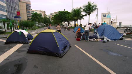 Рио : Slow dolly shot of crowd of protesters on the street. Some tents and buildings are seen in the video.