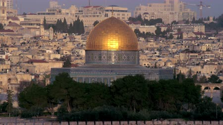 церковь : A medium shot of the Dome Of The Rock on the Temple Mount in Jerusalem,Israel,just as the sun kisses the golden dome. Shot from the east looking west with a long lens. Shot with the Red One digital camera at 4k 4096 x 2304 resolution. 02262011 Стоковые видеозаписи