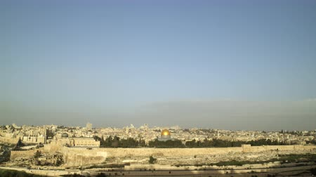 jerozolima : Tilt down from the Israeli sky to a wide shot of Old Jerusalem just as the sun illuminates the eastern wall of the Temple Mount. The cemetery on the Mount of Olives is still under shadow in the foreground. Shot with the Red One digital camera at 4k 4096 x Wideo
