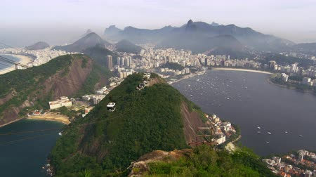 brazília : Gondola ascending along the side of Sugarloaf Mountain in Rio de Janeiro, Brazil. The Lagoa Rodrigo de Freitas is seen in the background.