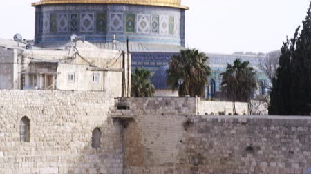 wailing wall : Tilt down from the golden dome of the Dome of the Rock on the Temple Mount to male Jews praying at the Western Wall,what is left of Solomons temple in Jerusalem,Israel. Shot with the Red One digital camera at 4k 4096 x 2304 resolution. 02262011 Stock Footage