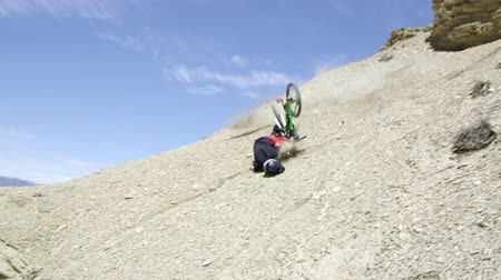 kask : Slow motion of a guy jumping from rocky ledge and crashing on mountain bike, then tumbling down hill. Stok Video