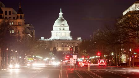 kormány : TIme lapse of the US Capitol at night with traffic moving.