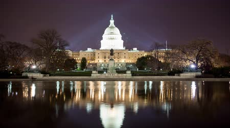 demokratický : Time lapse of the US Capitol at night with reflection and light rays.