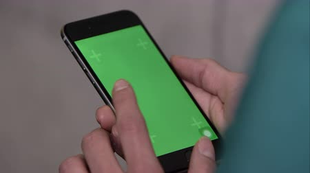 osoba : Up close shot of someone using smartphone with green screen. holding vertical and swiping.