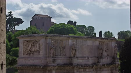 arch of constantine : The carvings on the top of the Arch of Constantine are visible from a window in the Colosseum. A building form the ruins on Palatine Hill can be seen in the background. Shot on May 6,2012