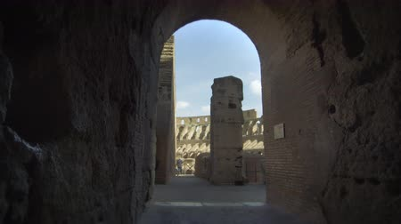 colloseum : Slow motion shot from a dark corridor in the Roman Colosseum of tourists walking around the Colosseum. Shot with a high speed camera on May 6,2012 in Rome,Italy Stock Footage