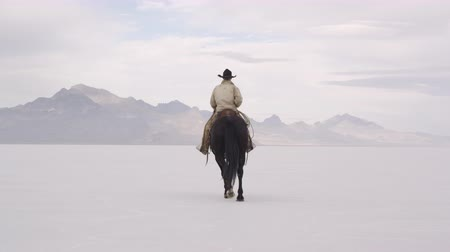 só : Slow motion of cowboy on horse turning around on the Bonneville Salt Flats in Utah.