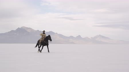 rachaduras : Slow motion of cowboy on horse standing and then starting to run on Bonneville Salt Flats in Utah.