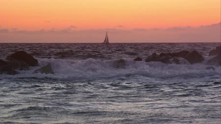 fala : Slow motion view of sailboat on the horizon at sunset.