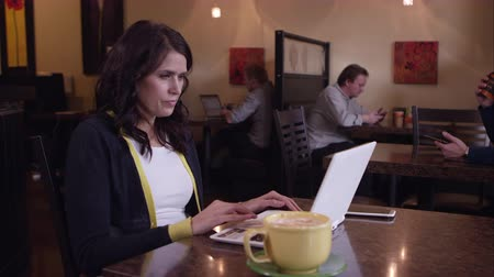 mysz : Panning view of woman in coffee shop using touch pad on laptop. Wideo