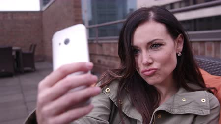 ona : Moving view of woman making kissing face as she poses for picture with smartphone.