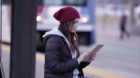 pěšina : Woman using tablet while sitting at trax stop in downtown. Dostupné videozáznamy