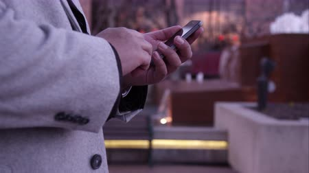 pěšina : View of mans hand typing on smartphone while walking down the sidewalk. Dostupné videozáznamy