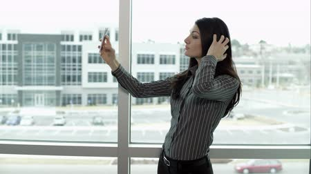 fotky : Woman taking photos with smartphone of herself posing.