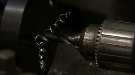 wiertarka : A close up of a machine drilling into metal. The drill is stationary while the metal is spinning.