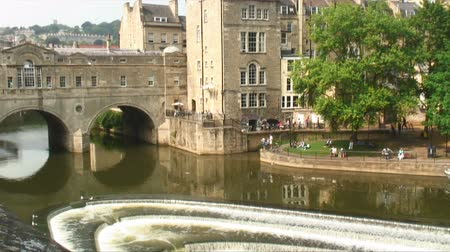 bretanha : Pan across the Pulteney Bridge and Weir with a ferry on the River Avon below. Also showing green trees and stone buildings of Bath, England. Vídeos