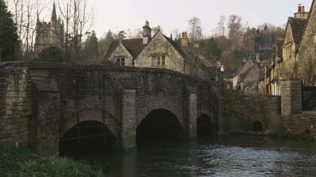 grzebień : Wide shot pan of old stone village, bridge and stream Wideo